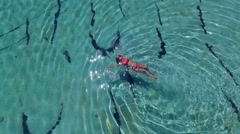 Young and beautiful fashion female model in red bikini lying on the waves in the - stock footage