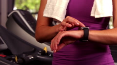 Stock Video Footage of Fit woman running on the treadmill with a connected watch