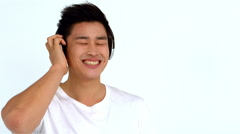 Smiling Asian man listening to music with headphones Stock Footage