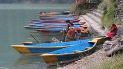 Three Nepali women unload wood from boat Stock Footage