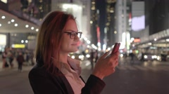 Young business women using smart phone while walking in the city at night - stock footage