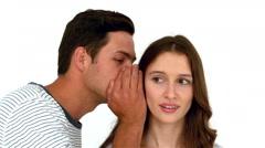 Man telling secret to surprised woman Stock Footage
