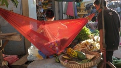 Kid in hammock at market stall with father,Siem Reap,Cambodia Stock Footage