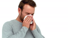 A Sick man sneezing into a tissue Stock Footage