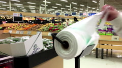 Woman taking plastic bag for buying food in grocery store - stock footage