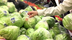 Woman selecting cabbage in grocery store Stock Footage