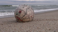 Vintage globe with America map on sand by the sea - stock footage