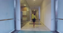 Woman in yellow jacket walking through modern building Stock Footage