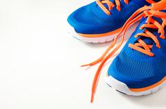 Blue sport running shoes with orange shoelace Stock Photos