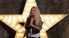 blonde woman singer with microphone, shining star in the background. slow motion - stock footage