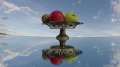 Antique vase on mirror under cloudy sky with fruits, time lapse 4K Stock Footage