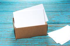 Business cards in brown paper box on wood desk - stock photo