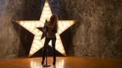 Stock Video Footage of singer with blonde curly hair, microphone, dances. shining star in the