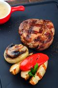 Grilled beef steak on wooden pan. Stock Photos