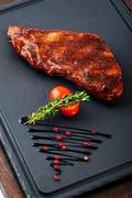 Grilled beef steak on wooden pan. - stock photo