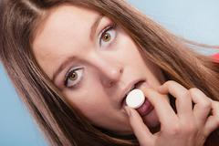 Woman taking painkiller pill tablet. Health care. - stock photo
