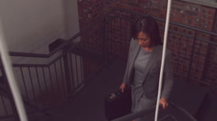 Unsmiling businesswoman going upstairs Stock Footage