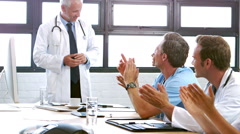 Smiling medical team applauding colleague Stock Footage