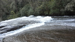 Fast flowing river panned to watefall Stock Footage