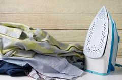 Laundry housework with pile of shirts and electric iron - stock photo