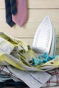 Laundry housework with pile of shirts and tie hanging Stock Photos