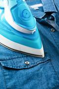 Ironing blue denim shirt with steam iron - stock photo