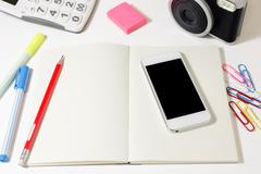 Work desk with blank notebook, phone, camera, calculator and pencil Stock Photos