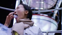 Young asian woman enjoying candy floss on a ferris wheel, in slow motion - stock footage