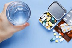 Pills on table with hand holding drinking water glass - stock photo