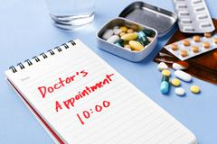Doctor appointment note with medicine pills on table - stock photo