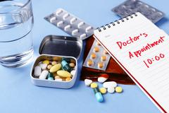 Pills with doctor appointment note on table Stock Photos