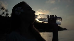 Silhouette of a Girl with a Flower in Her Hair Drinking Water from a Plastic Stock Footage
