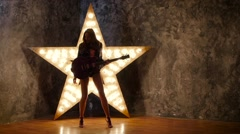 Girl dancing with electric guitar, shining star in the background. slow motion Stock Footage
