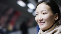 Young asian woman's smiling face as she travels on a moving sidewalk Stock Footage