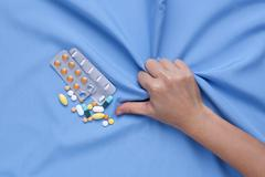Closeup hand with pain and suffer from illness with medicine pills - stock photo