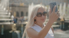 Gorgeous Woman clicking selfie on the phone next to the fountain in Peterhof Stock Footage