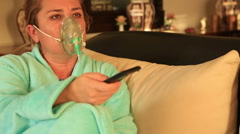 Woman with oxygen mask watching tv Stock Footage