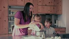 Mother making a cake with her children happy Stock Footage