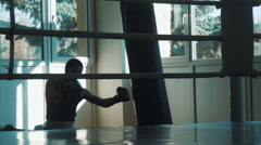 Silhouette of young boxer training with punching bag in gym look through a ring Stock Footage