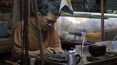 Man repairing jewelry in market,Siem Reap,Cambodia Stock Footage