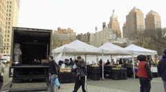 Union Square farmers market on cold fall winter day with people walking in crowd Stock Footage