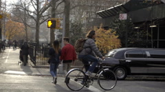 Man bicycling on bike down Mercer Street past stretch limousine in New York City Stock Footage