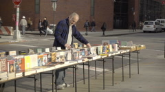 Man selling books on table in Greenwich Village outside NYU in New York City Stock Footage