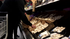 Man selecting mushroom in grocery store produce department - stock footage