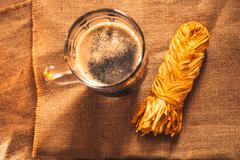 A glass of fresh dark beer with smoked cheese plait on sacking Stock Photos