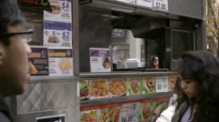 Silhouette of man cooking and preparing food in Halal cart outside NYU in NYC Stock Footage