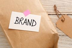 Brand marketing concept with product package, brand tag on wood desk Stock Photos
