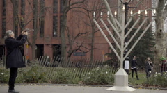 Woman taking picture of giant Menorah on 6th night of Hanukkah in park Stock Footage