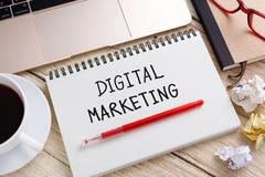 Stock Photo of Digital marketing handwriting note with laptop on office desk