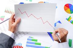 Businessman observing a chart with a downward trend Stock Photos